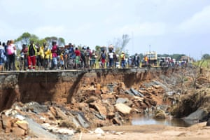 People pass through a section of the damaged road in Nhamatanda, about 30 miles from Beira