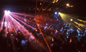 Pink, red and yellow laser lights over a dancing crowd