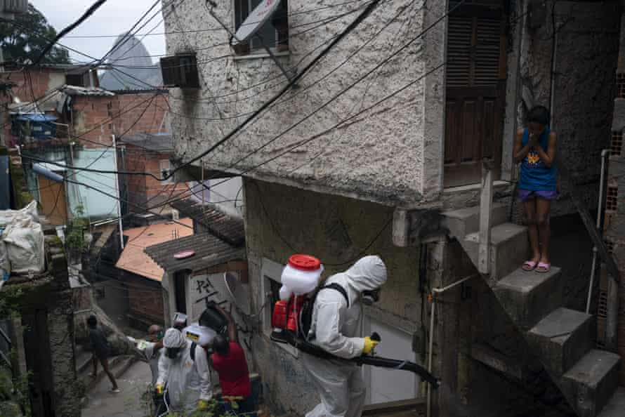 Thiago Firmino and other volunteers spray disinfectant in an alley to help contain the spread of coronavirus in the Santa Marta slum in Rio de Janeiro, Brazil, Friday, 10 April 2020