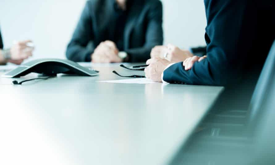 Executives sit at a boardroom table