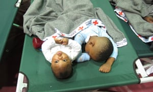 Five-month-old Jeremiah Odum, left, and his two-year-old brother, Braxton Odum, nap on a cot in a high school gymnasium being used as a Red Cross shelter for flood evacuees in Rowesville, South Carolina.