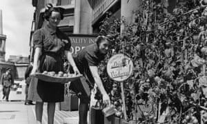 Waitresses at the Quality Inn, Regent Street, London, watering tomatoes as part of the 'Dig For Victory' scheme in 1942.