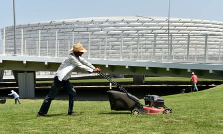Gardeners cut the grass in front of Azerbaijan's Olympic Stadium, which seats around 68,000 although Baku airport can only deal with around 15,000 arrivals a day.