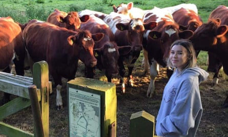 Nina Bunting-Mitcham stands with a group of cows.