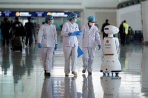 Medical workers walk by a police robot at Wuhan Tianhe international airport