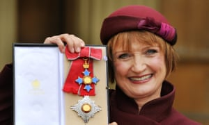Tessa Jowell holds up her Dame Commander insignia at Buckingham Palace in 2013
