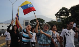 Sympathizers of Venezuelan interim President Juan Guaido wave the Venezuelan national flag outside the military base of La Carlota, where Guaido remains inside backed by a group of military personnel