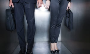 Colleagues holding hands in elevator