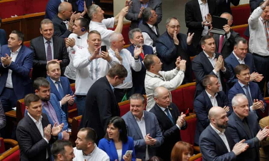 Lawmakers clap and smile in Ukraine's parliament