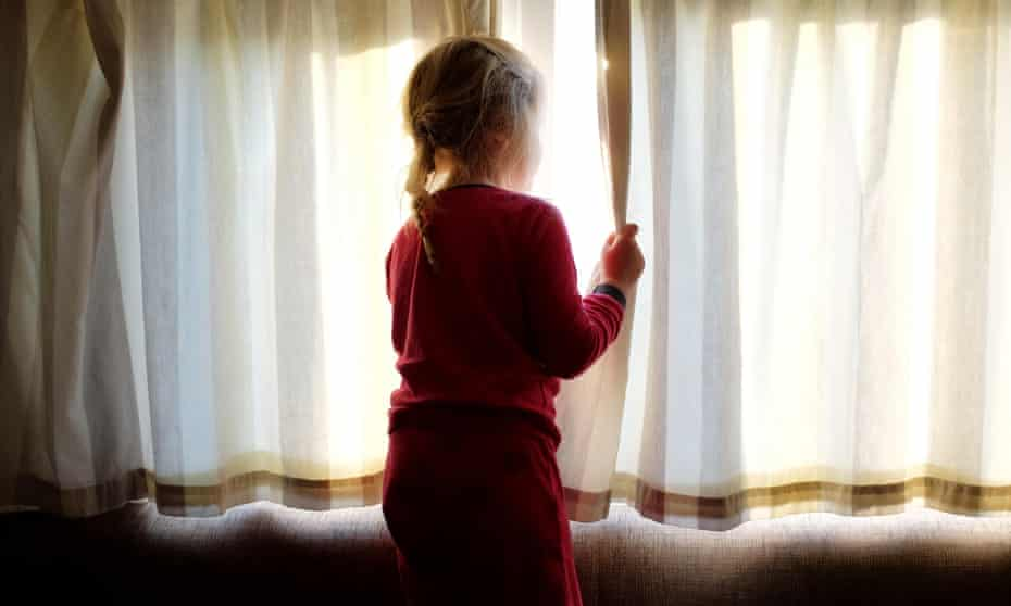 A young girl in pyjamas opening curtains