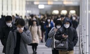 Pedestrians wearing face masks walk through an underground passage on in Tokyo, Japan