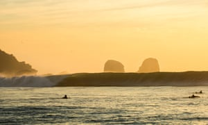Surfers in the ocean at sunset, Pichilemu, Chile.