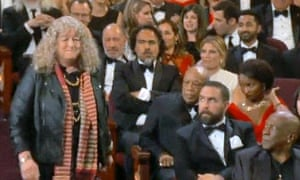 Wear it with pride: Jenny Beavan ignores the looks of disdain from fellow guests as she collects her Oscar.