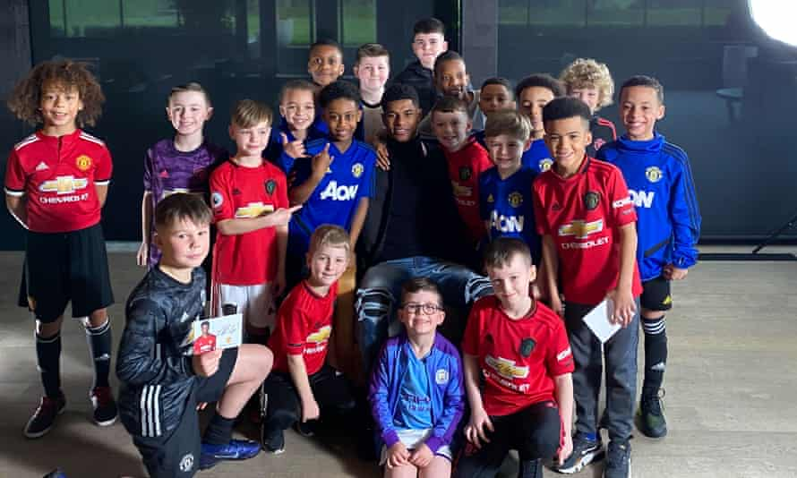 Marcus Rashford poses with a gorup of children after a press conference