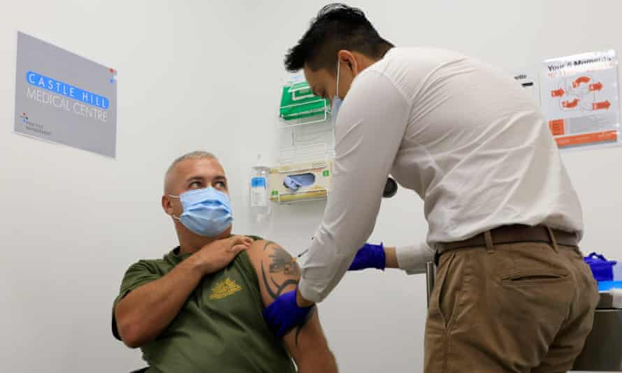 man receives covid vaccine in a doctor's surgery