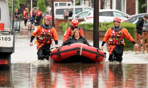 A woman is rescued from her flooded property in Romford