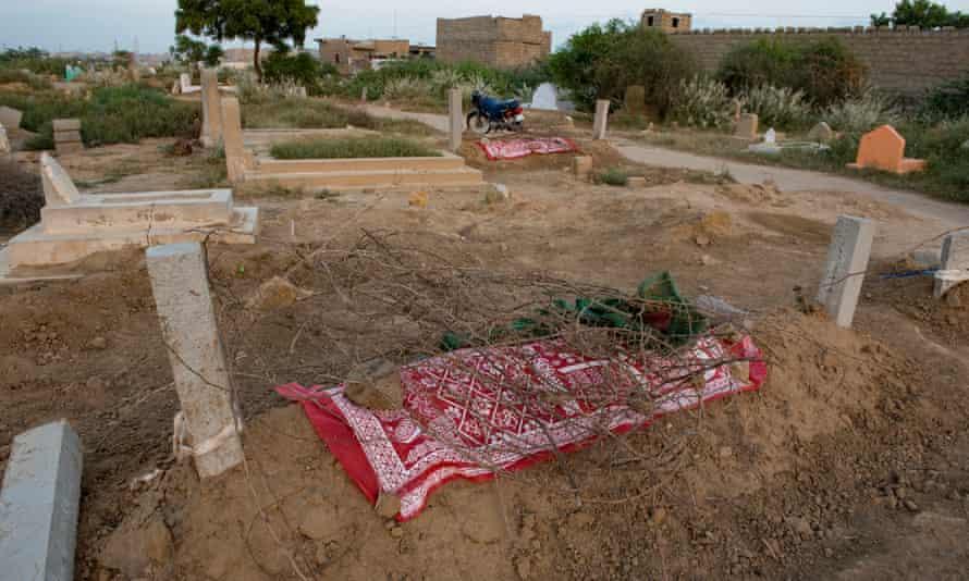 The graves of Ghani Rehman, 17, and Bakhtaja, 15, in Ali Brohi Goth, Karachi