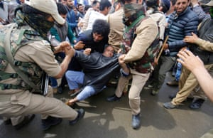 Police officers try to detain a supporter of Engineer Rashid during a protest in Srinagar, India