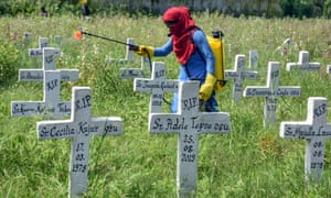 A municipal worker sanitises a Roman Catholic Church graveyard after the burial of Covid-19 coronavirus infected people in Ranchi
