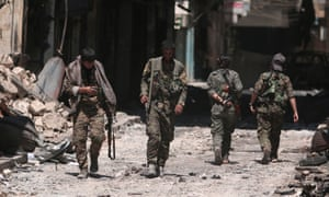 Syria Democratic Forces (SDF) fighters walk on the rubble of damaged shops and buildings in Manbij, Syria.