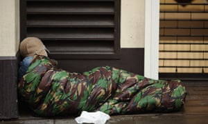 A homeless man sleeps near Trafalgar Square in London