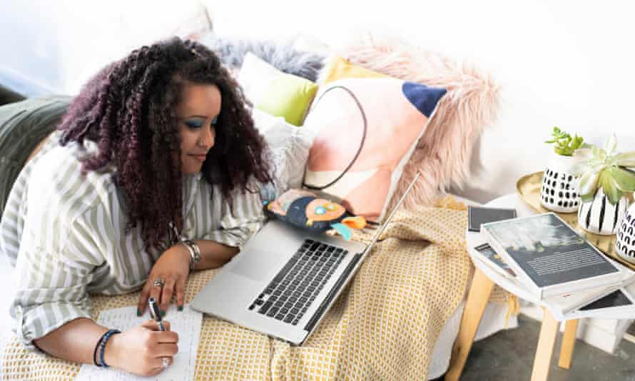 A woman lies on a bed working on her laptop