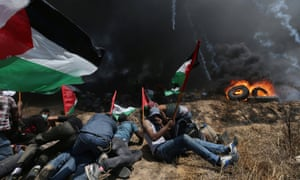 Palestinian demonstrators take cover from Israeli fire in the southern Gaza Strip.