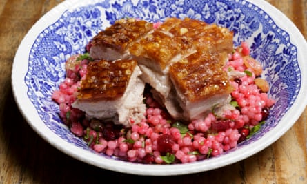 pork belly with giant couscous, cider-soaked golden raisins, beetroot and pomegranate on a plate