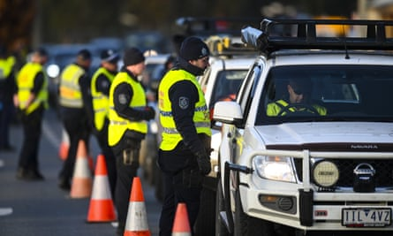 NSW police officers check cars crossing from Victoria at a border checkpoint in town of Albury on Wednesday.