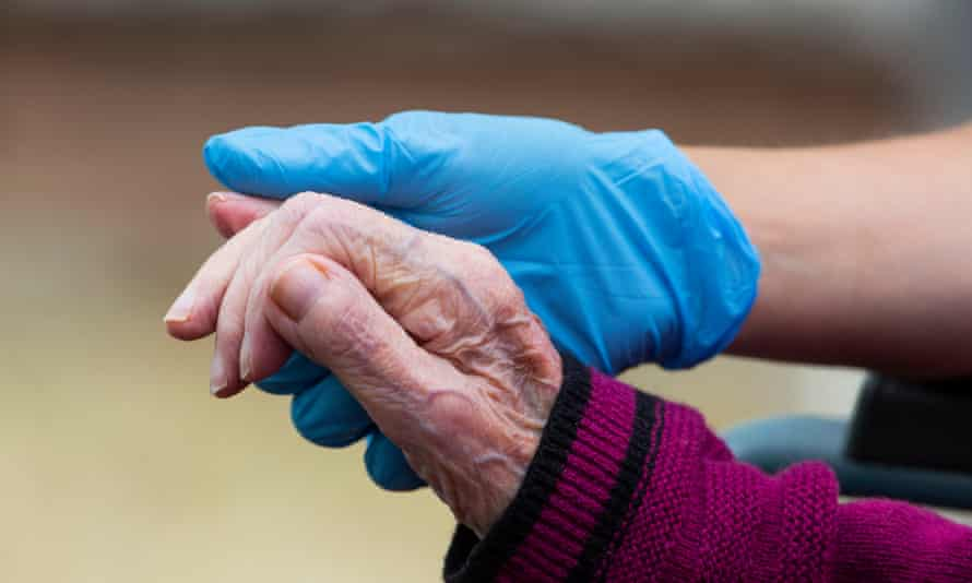 Carer hold a resident's hand