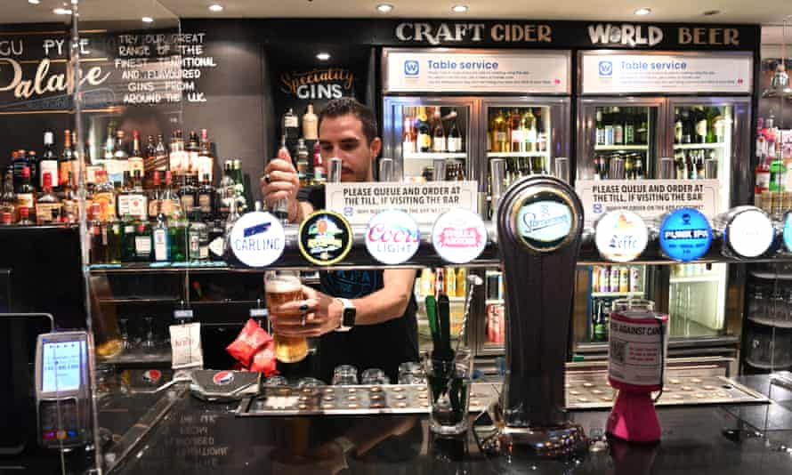Barman pulls a pint in a pub.
