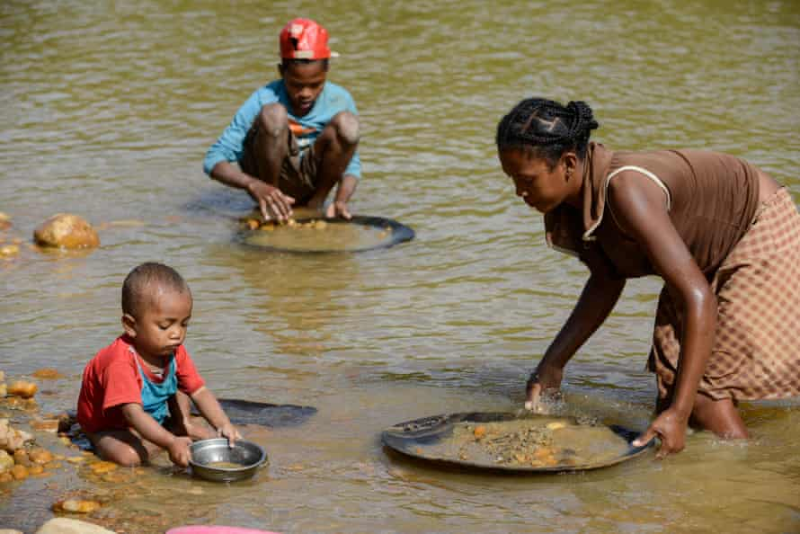 Children and a woman pan for gold in the river near the Madagascan city of Mananjary, June 2015.