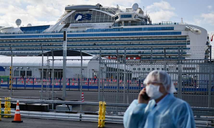 A man in protective gear speaks on the phone near the Diamond Princess cruise ship.