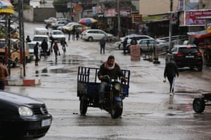 Palestinians walk in a street flooded by rain water in Dair Al Balah in the central of Gaza Strip. The bad weather and snow has caused damage to homes, mainly in the Gaza Strip, and forced the government and banks to call off work.