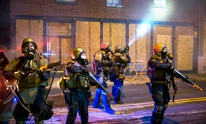 Police officers react to violent protesters during a second night of protests in Ferguson, Missouri