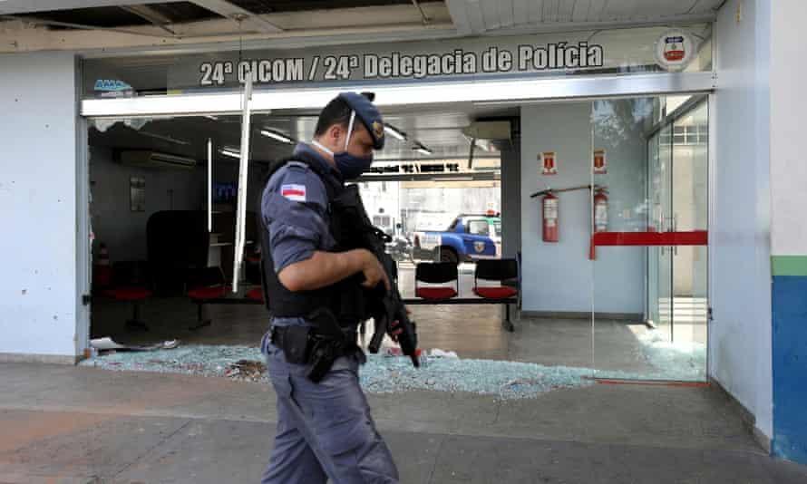 Un policier surveille le devant d'un poste de police qui a été endommagé à Manaus, au Brésil, lundi.