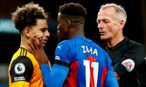Referee Martin Atkinson (right) intercedes as Crystal Palace's Wilfried Zaha (centre) confronts Wolves goalscorer Rayan Aït-Nouri.