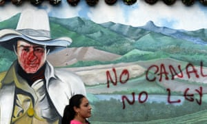 A woman is seen in front of a mural of national hero Augusto César Sandino with graffiti reading 'No canal, no law' during a protest against the construction of an inter-oceanic canal in Juigalpa, Nicaragua on 13 June 2015.