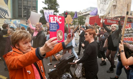An anti-abortion supporter holds up leaflets as pro-choice demonstrators march in Belfast in September