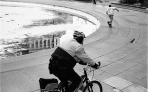 A Police officer chases a skateboarder.