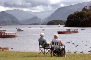A couple relax on the bank of Derwentwater, the third largest lake in the region