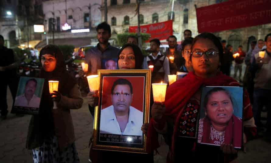 Survivors and relatives of victims of the Bhopal gas accident hold photos of the victims during a candlelight vigil.