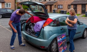 A mother watches her son unpack the car as he arrives at university