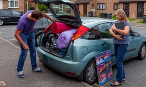 A mother watching her student son pack a car full of his stuff
