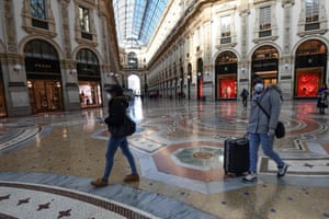 Tourists wearing protective face masks walk in Galleria Vittorio Emanuele II in the centre of Milan