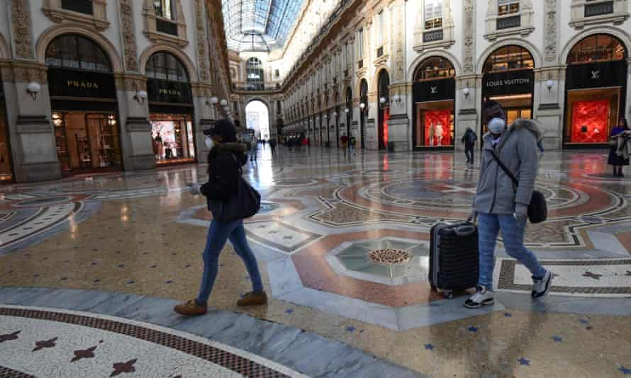 Tourists wearing protective face masks walk in Galleria Vittorio Emanuele II in the centre of Milan.