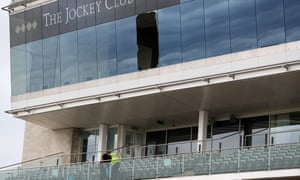 Workers clear up after a window fell out of the Champions Gallery on the third floor on to the level two seating at Newmarket.