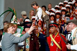 Berlin, Germany: Angela Merkel meets a marionette during a carnival reception at the Chancellery
