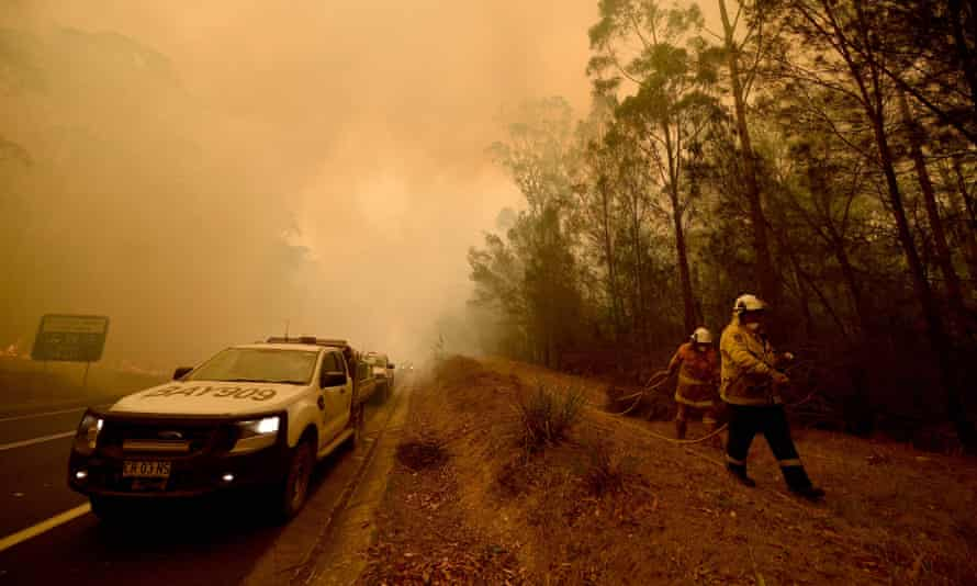 Firefighters tackle a bushfire in thick smoke in the New South Wales town of Moruya