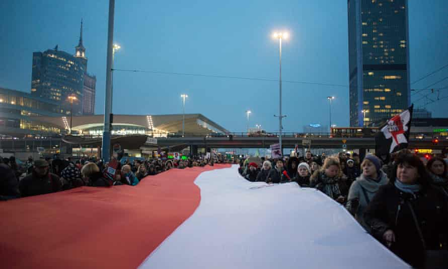 A giant Polish flag is unfurled by people protesting in Warsaw last month against plans to further restrict abortion laws in Poland.